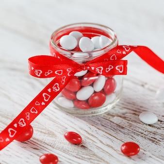 Tarro de caramelo colorido decorado con un lazo rojo corazones. concepto de día de san valentín