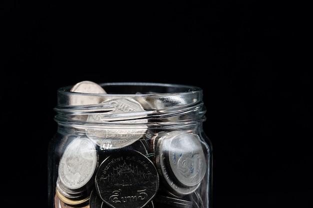 Tarro claro lleno de monedas de baht tailandés sobre fondo negro