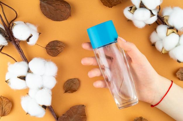Tarro cosmético en mano, algodón y hojas.