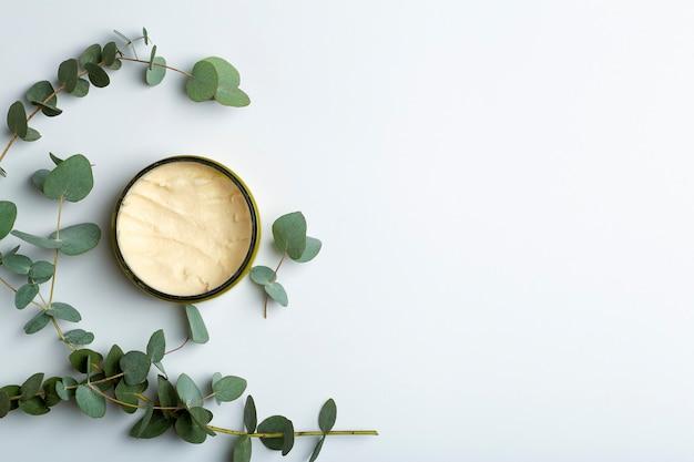 Tarro de cosméticos con ramas de eucalipto sobre fondo blanco.