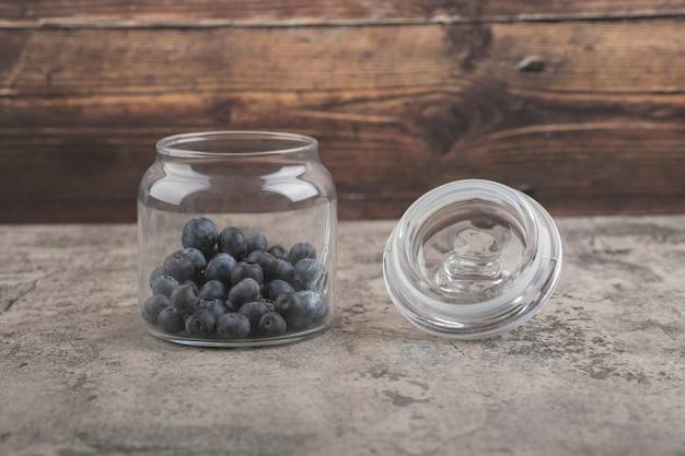 Tarro de cristal de deliciosos arándanos frescos en la superficie de mármol