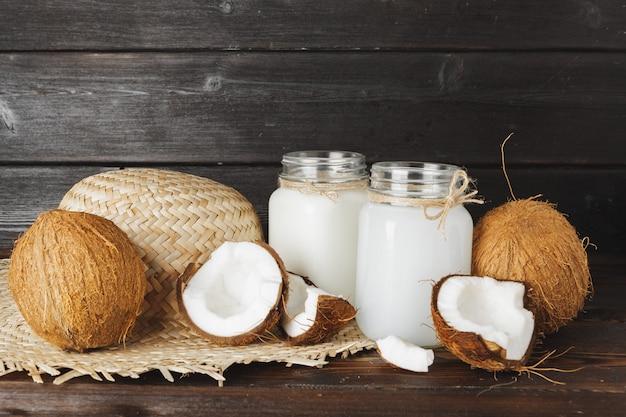 Tarro de cristal de leche de coco de cerca sobre la superficie de madera
