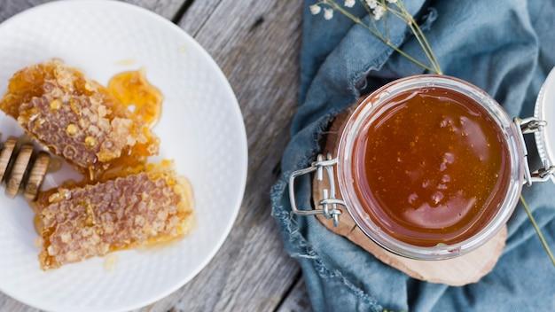 Tarro de cristal lleno de miel con cuchara de miel