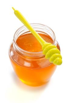 Tarro de cristal lleno de miel y palo aislado sobre fondo blanco.