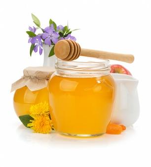 Tarro de cristal lleno de miel y palo