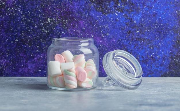 Tarro de cristal de malvaviscos de colores suaves sobre fondo de mármol