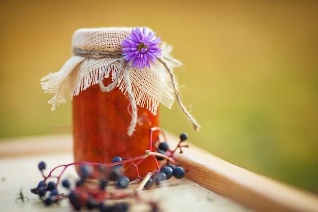 Tarro de cristal con mermelada de albaricoque sabroso sobre una mesa. otoño