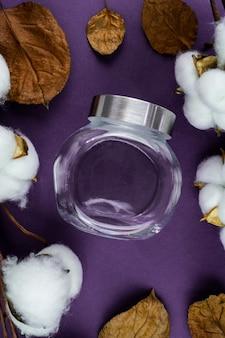 Tarro de cristal, mesa de algodón y violeta