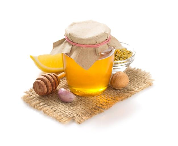 Tarro de cristal de miel aislado en blanco