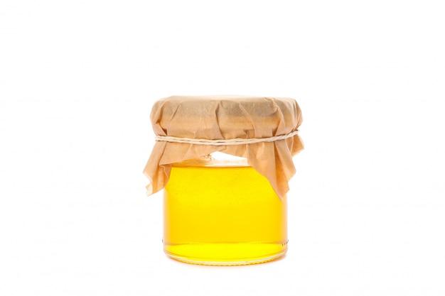 Tarro de cristal con miel aislado en blanco