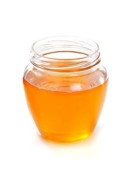 Tarro de cristal de miel aislado sobre fondo blanco.