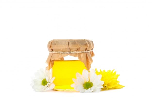 Tarro de cristal con miel, crisantemo y manzanilla aislado en blanco