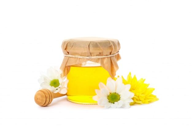 Tarro de cristal con miel, crisantemo, manzanilla y cazo aislado en blanco