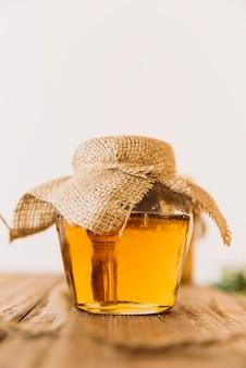 Tarro de cristal de miel dulce en mesa de madera