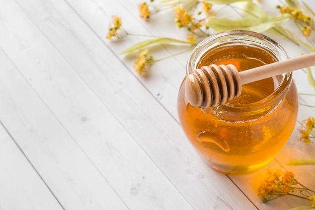 Tarro de cristal de miel, flores de tilo.