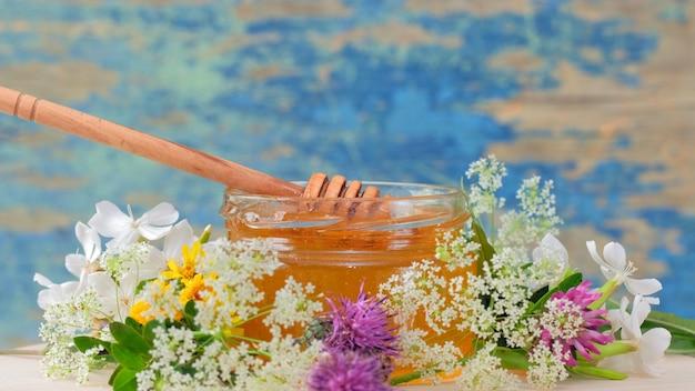 El tarro de cristal con miel fresca en el fondo rústico. flores sobre la mesa.