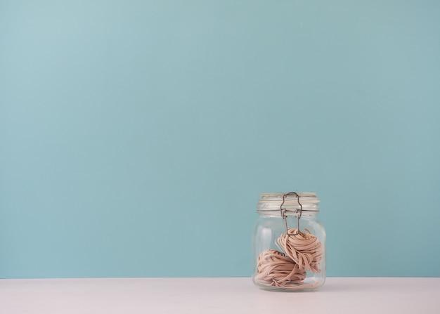 Tarro de cristal con pasta nido de tallarines de trigo integral.