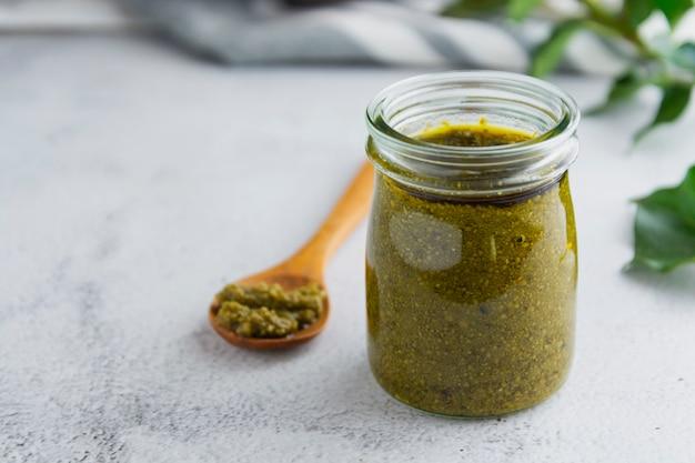 Tarro de cristal con salsa de pesto en blanco con textura de fondo tabla de cerca. salsa para pasta. copia espacio