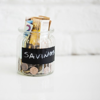 Tarro de cristal de ahorro con billetes y monedas en el fondo blanco