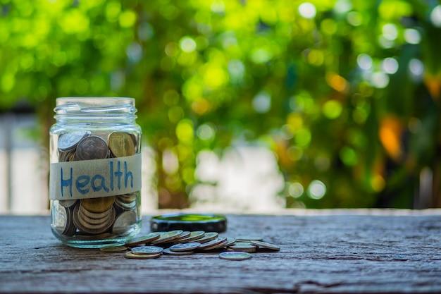 Tarro de dinero con monedas en mesa de madera, concepto de salud
