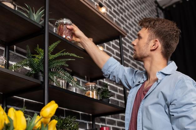 Tarro con especias. apuesto joven barbudo vestido con camisa azul poniendo tarro con especias en el estante