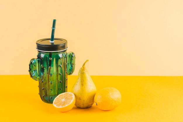 Tarro de forma de cactus con peras y limones sobre fondo amarillo
