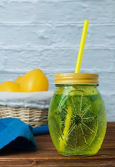 Un tarro de jugo de limón con hojas, tela azul, limones en canasta sobre superficie de madera y blanca, vista lateral. espacio para texto