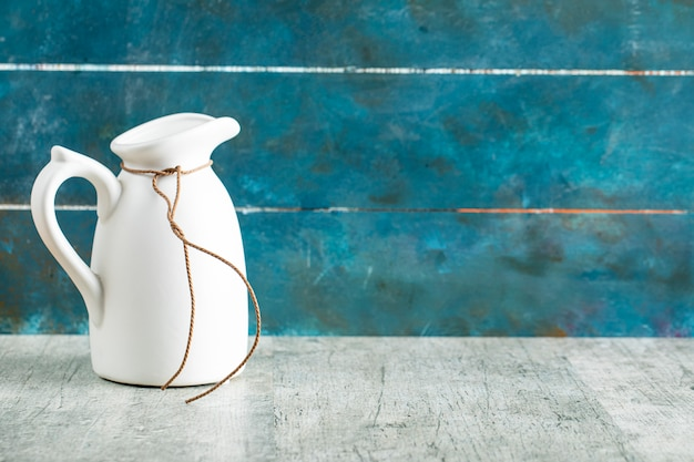 Un tarro de leche de cerámica blanca en mesa rústica