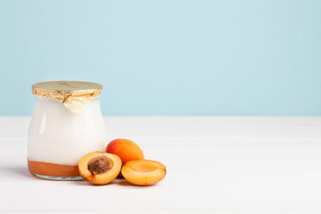Tarro de leche fresca y fruta de albaricoque.