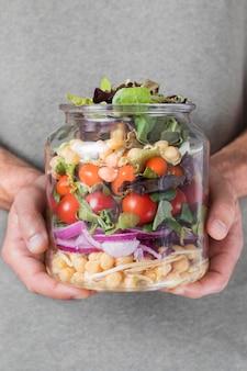 Tarro lleno de varias frutas y verduras.