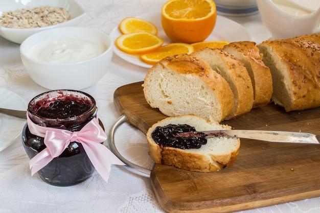 Tarro de mermelada de grosella en mesa con barra de pan