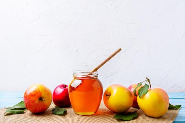 Tarro de miel con cucharón y manzanas sobre fondo blanco.