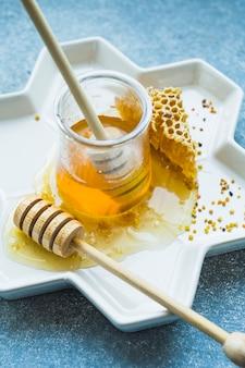 Tarro de miel con cucharón de miel y peine de miel en bandeja floral