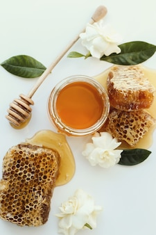 Un tarro de miel con flores alrededor.