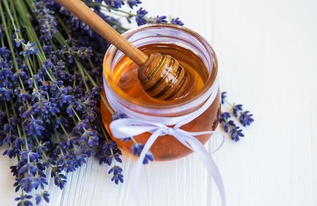 Tarro con miel y flores frescas de lavanda.
