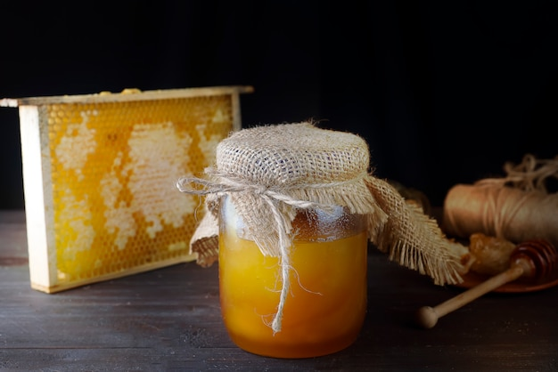 Tarro de miel líquida con panal.