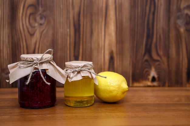Tarro de miel y mermelada de frambuesa con limón fresco sobre madera