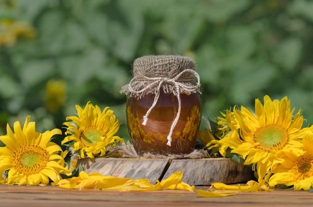 Tarro de miel y palo de madera en mesa contra verde borrosa natural