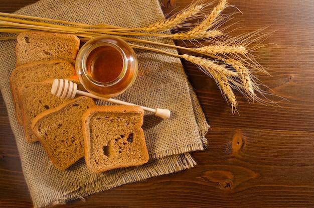Tarro con miel, pan de centeno, una cucharada de miel y espiguillas sobre tela de saco, mesa de madera
