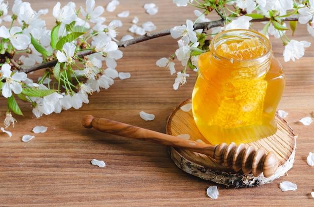 Tarro de miel con panal y cucharón de miel con flores de cerezo.