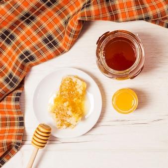 Tarro de miel; panal; cucharón de miel y mantel sobre escritorio blanco