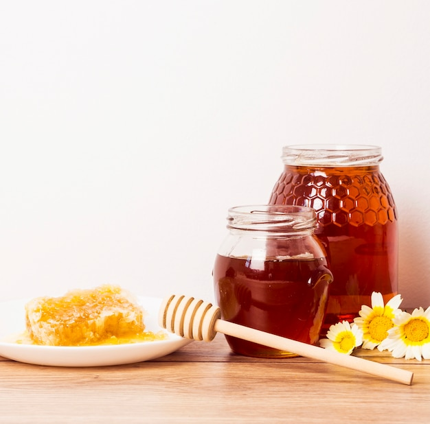 Tarro de miel y panal con cucharón de miel en la mesa de madera