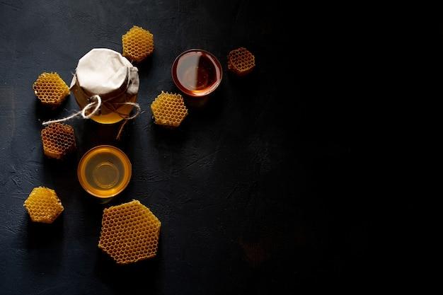 Tarro de miel con panal en mesa negra