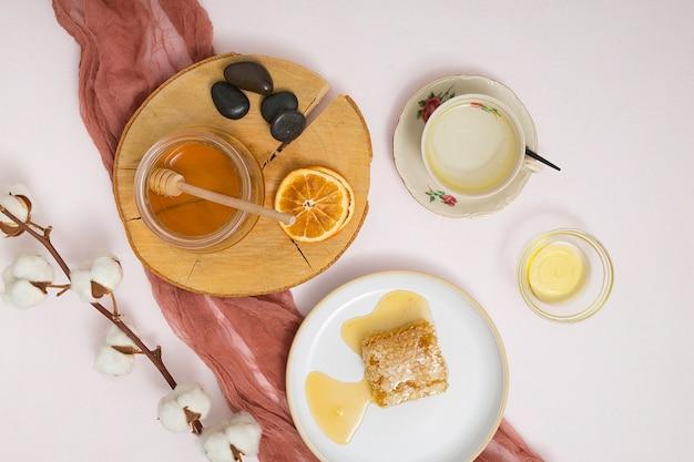 Tarro de miel; rodajas de cítricos secos; los últimos; panal de miel y rama de algodón sobre fondo blanco