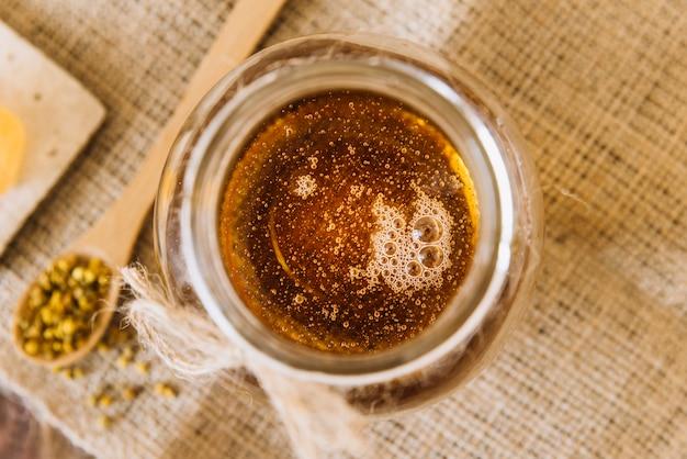 Tarro de miel y semillas de polen de abeja.