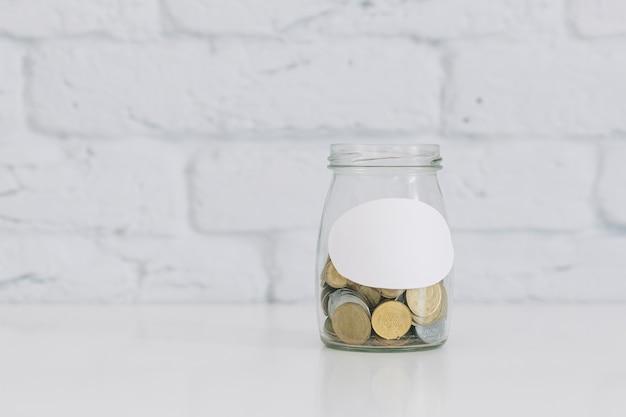 Tarro de la moneda en el escritorio blanco contra la pared blanca