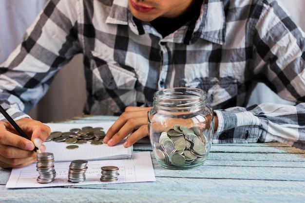 Tarro con monedas de ahorro en la mesa