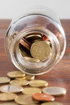 Tarro con monedas en la mesa
