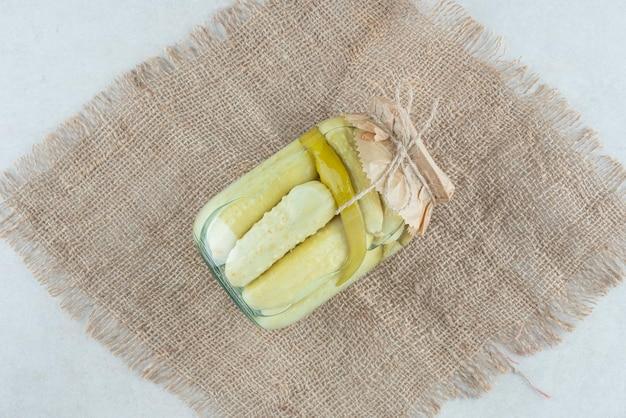 Un tarro de pepinos encurtidos caseros sobre arpillera.
