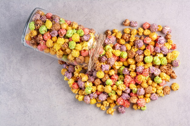 Tarro pequeño de palomitas de maíz derramado sobre mármol.
